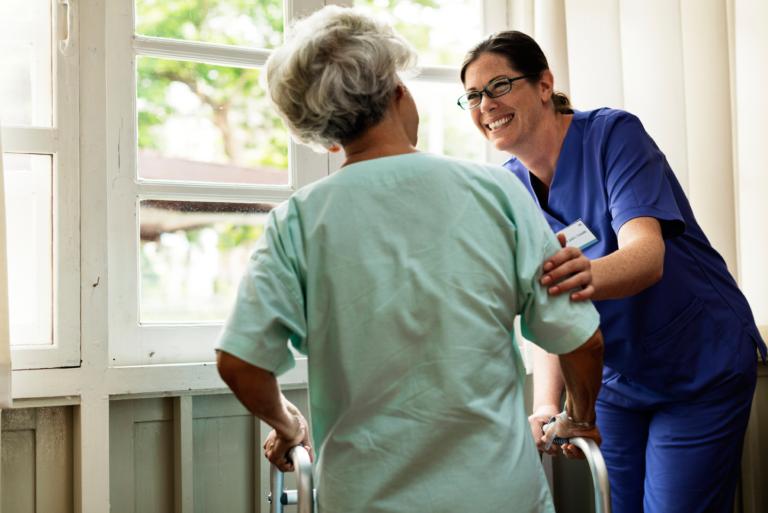 nurse helps elderly patient using a walker